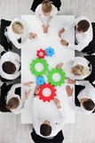 Business team with cogs. Business team sitting around the table with cogs, teamwork concept Royalty Free Stock Photo