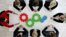 Business team with cogs. Business team sitting around the table with cogs, teamwork concept stock footage
