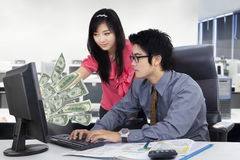 Business team with computer and dollars. Image of Asian business team working together in the office and earning dollars cash on the computer Stock Image