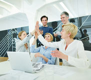 Business team with computer giving High Five Royalty Free Stock Image