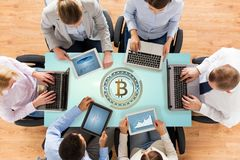 Business team with computers and bitcoin hologram Stock Photos