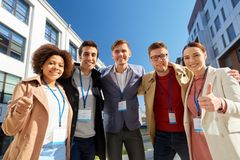 Business team with conference badges in city. Business, corporate and success concept - international group of people with name tags or conference badges showing Royalty Free Stock Image