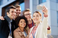 Business team with conference badges taking selfie Stock Photo