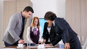 Business team in conference room looking at papers with charts stock video