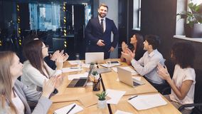 Business team congratulating successful leader with applause. At conference meeting stock photos