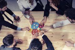 Business team connect pieces of gears. Photo from above. Teamwork, partnership and integration concept. Teamwork of businesspeople work together and combine stock image