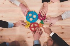 Business team connect pieces of gears. Teamwork, partnership and integration concept. Teamwork of businesspeople work together and combine pieces of gears stock images
