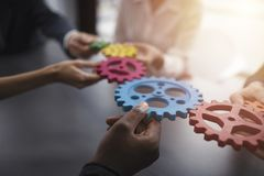 Business team connect pieces of gears. Teamwork, partnership and integration concept. Teamwork of businesspeople work together and combine pieces of gears stock image