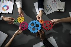 Business team connect pieces of gears. Teamwork, partnership and integration concept. Teamwork of businesspeople work together and combine pieces of gears stock photography