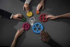 Business team connect pieces of gears to build a new creative idea. Teamwork, partnership and integration concept. Teamwork of businesspeople work together and stock image