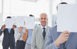 Business team covering face with white paper except for one Stock Photography