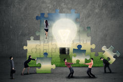 Business team creating a puzzle. Business teamwork creating a puzzle together Stock Photo