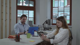 Business team at daytime indoors. Two designers sitting in the office. Happy coworkers working and talking discussing project. Smiling professional woman stock footage