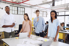 Business team at desk in an office look to camera, close up Royalty Free Stock Photo