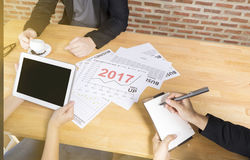 Business team discussing analyze financial report graph year 2017 trend forecasting planning in cafe coffee shop Royalty Free Stock Photos