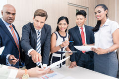 Business team discussing graphs and numbers in meeting Royalty Free Stock Photo