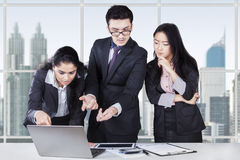 Business team discussing with laptop. Multicultural business team standing in office while discussing with laptop on desk Royalty Free Stock Images