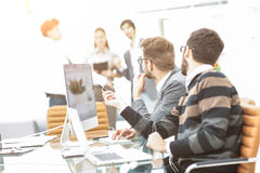 business team discussing marketing schemes in the workplace on the background of the company`s employees Stock Photography