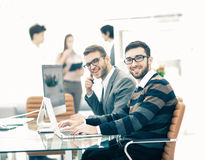 business team discussing marketing schemes in the workplace on the background of the company`s employees Royalty Free Stock Photos