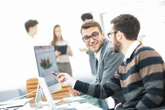 business team discussing marketing schemes in the workplace on the background of the company`s employees Royalty Free Stock Photography