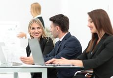 Business team discussing new information , standing in front of the open laptop. In the office Stock Photography