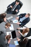 Business team discussing in office financial issues. Business team at a briefing discussing financial charts stock photography