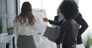 Business team discussing with reports on whiteboard at office. Business colleagues discussing with financial reports on whiteboard at office meeting stock video footage