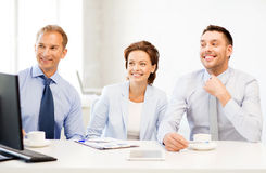Business team discussing something in office. Smiling business team discussing something in office Stock Images