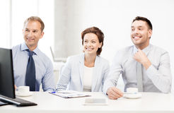 Business team discussing something in office. Smiling business team discussing something in office Royalty Free Stock Images