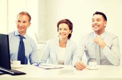 Business team discussing something in office. Smiling business team discussing something in office Stock Photo