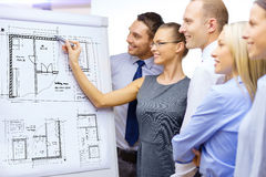 Business team drawing bluepring on flip board. Business, construction, building and office concept - smiling business team drawing blueprint on flip board and royalty free stock image