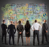 Business team drawing a new complex project. On wall royalty free stock photography