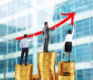 Business team draws growing arrow of company statistics over the piles of money. Business team draws red growing arrow of company statistics over the piles of royalty free stock image