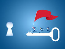 Business team with flag running on big key to target and success point. Key to success concept. Royalty Free Stock Photography