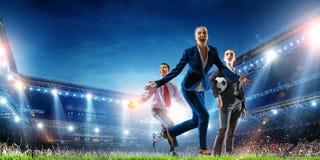 Business team on football stadium. Mixed media stock images