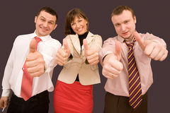 Business team in formal suits with thumbs up Royalty Free Stock Images