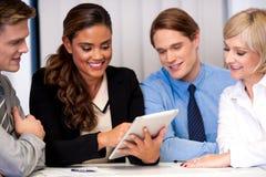 Business team of four enjoying work Stock Image