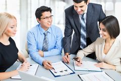 A business team of four plan work. In office Royalty Free Stock Image