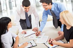 Business team. A business team of four plan work in office Stock Photography