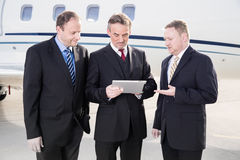 Business team in front of corporate jet looking at tablet comput Stock Photography