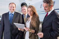 Business team in front of corporate jet looking at tablet comput Royalty Free Stock Photo
