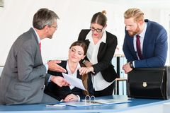 Team gathers around a desk, discussing a document Stock Images