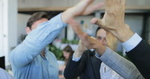 Business team giving each other high five cheering of successful deal modern office, mix race businesspeople group