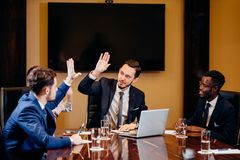 Business team giving high fives gesture as they laugh and cheer their success. Group of executives smiling and group high fiving Royalty Free Stock Photos