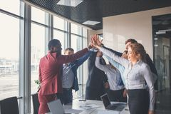 Business team giving a high fives gesture as they laugh and cheer their success Royalty Free Stock Images