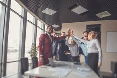 Business team giving a high fives gesture as they laugh and cheer their success Royalty Free Stock Photo