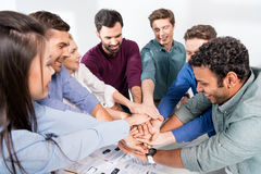 Business team giving highfive together on workplace in office. Young professional group concept Royalty Free Stock Photos