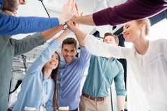 Business team giving highfive together on workplace in office Royalty Free Stock Images