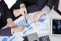 Business team hands pointing pie chart. Closeup of businesspeople hands pointing a pie chart together on the paperwork Royalty Free Stock Images