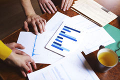 Business team hands at work with financial reports and a tablet Stock Photos